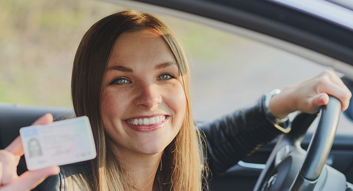 Young lady holding her new driver license in a car